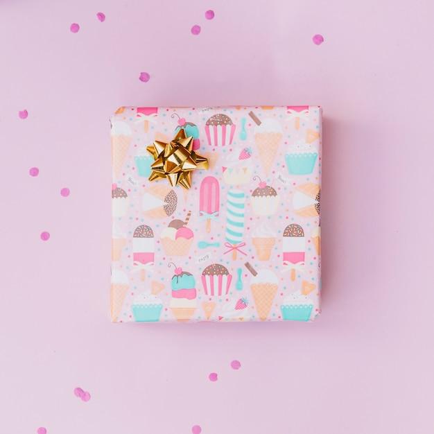 Arco dorado en caja de regalo envuelta sobre fondo rosa Foto gratis