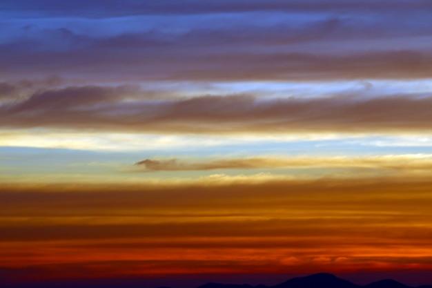 El arco iris y el cielo azul rojo naranja amarillo nube en puesta de sol en la montaña Foto Premium