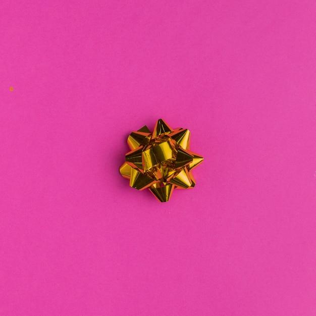 Arco de regalo dorado sobre fondo rosa brillante Foto gratis