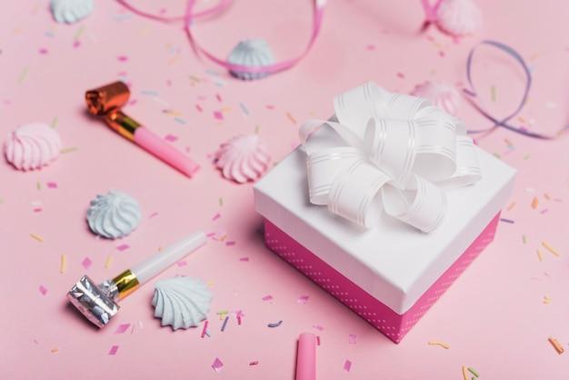 Arco de satén blanco en caja de regalo con soplador de fiesta y caramelos sobre fondo rosa Foto gratis