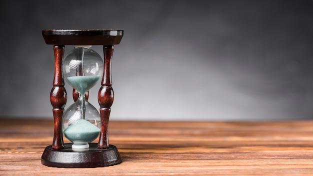 Arena transparente reloj de arena en el escritorio de madera contra el fondo gris Foto gratis