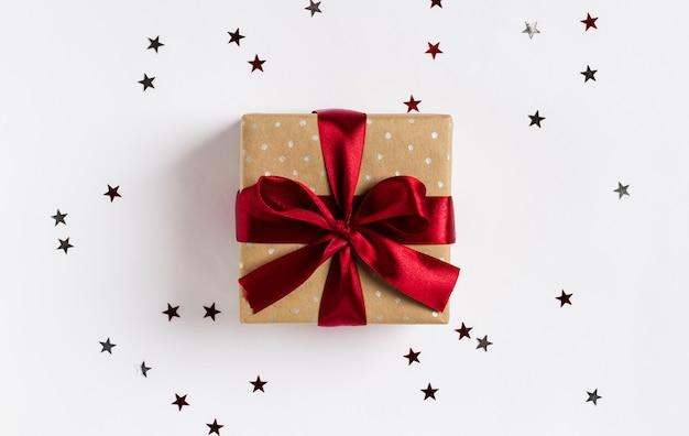 Arqueamiento rojo de la caja de regalo de vacaciones de navidad en mesa festiva decorada con estrellas de destellos Foto gratis