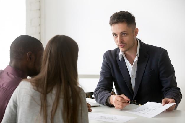Arquitecto, agente inmobiliario o diseñador que consulta a una pareja interracial con el plan de la casa. Foto gratis