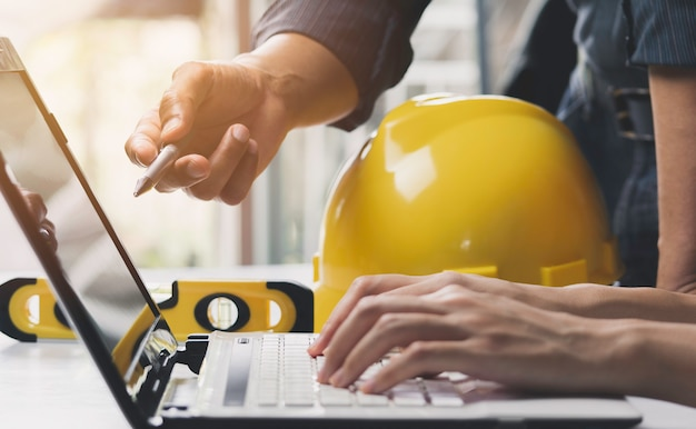Arquitecto ingeniero trabajando concepto y herramientas de construcción o equipo de seguridad en la mesa. Foto Premium