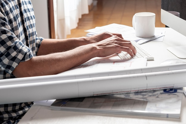 Arquitecto mirando su proyecto en su escritorio Foto gratis