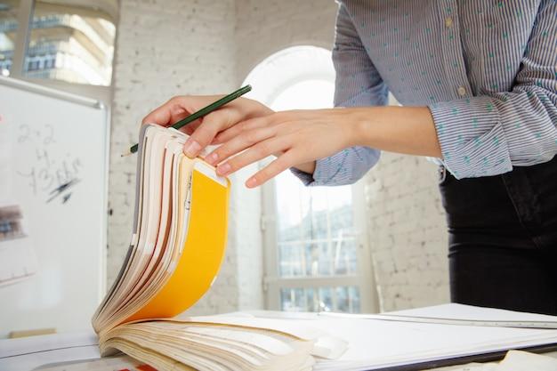 Arquitecto o diseñador de interiores profesional que trabaja con paleta de colores, dibujos de habitaciones en la oficina moderna Foto gratis