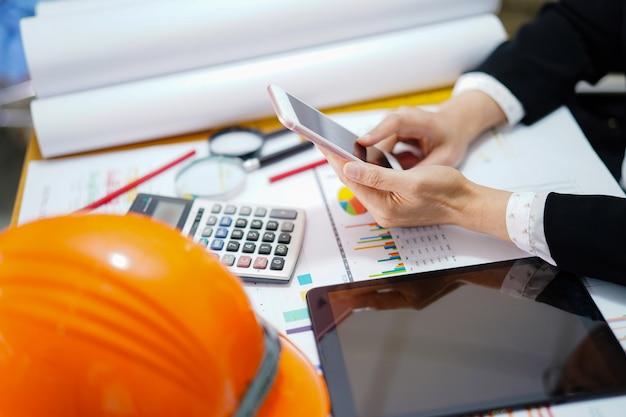 Arquitecto o ingeniero que trabaja el proyecto de contabilidad con el gráfico en la oficina. Foto Premium