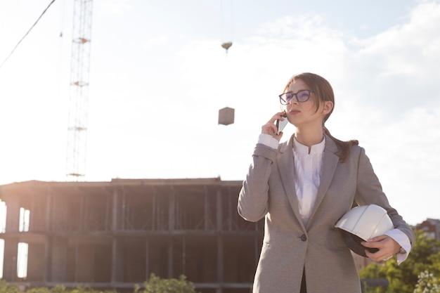 Arquitecto de sexo femenino atractivo joven que habla en el teléfono móvil en el emplazamiento de la obra Foto gratis