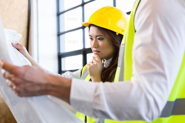 Arquitectos mirando planos en la oficina Foto Premium