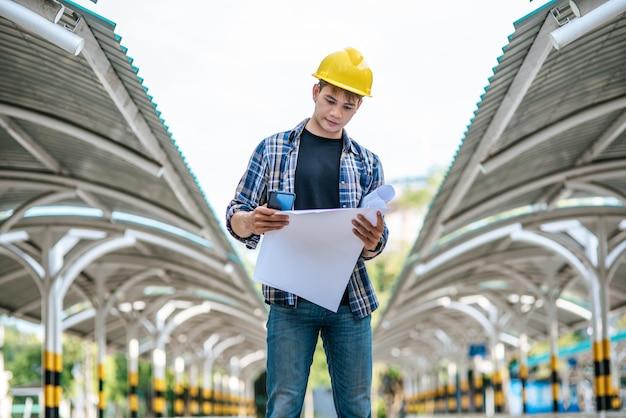 Los arquitectos sostienen el plan de construcción y verifican el trabajo. Foto gratis