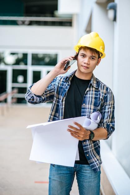 Los arquitectos tienen planos de planta y hablan por teléfono. Foto gratis