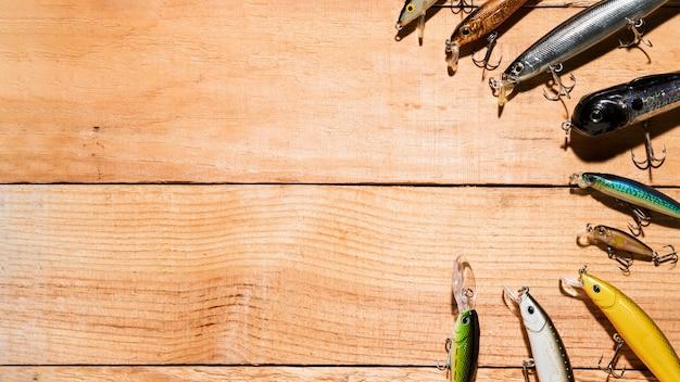 Arreglado colorido señuelo de la pesca en el escritorio de madera Foto gratis