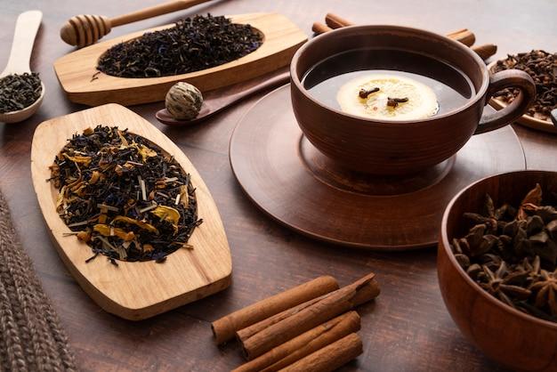 Arreglo de alto ángulo con una taza de té y hierbas Foto gratis