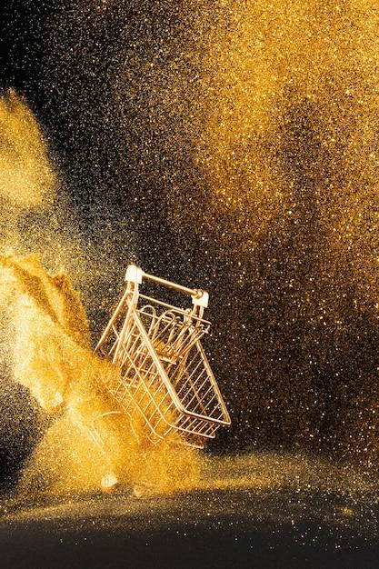 Arreglo de carro de compras dorado con purpurina dorada Foto gratis