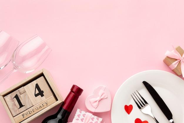 Arreglo para la cena del día de san valentín sobre fondo rosa con espacio de copia Foto gratis