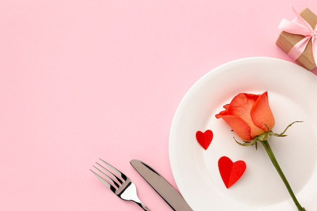 Arreglo para la cena del día de san valentín sobre fondo rosa con rosa naranja Foto gratis