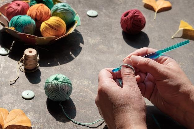 Arreglo creativo de materiales artesanales para tejer y crochet en mesa oscura. Foto Premium