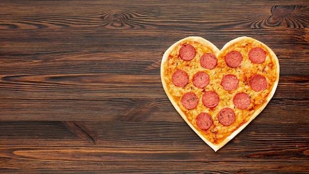 Arreglo encantador para la cena del día de san valentín con pizza en forma de corazón y espacio de copia Foto gratis