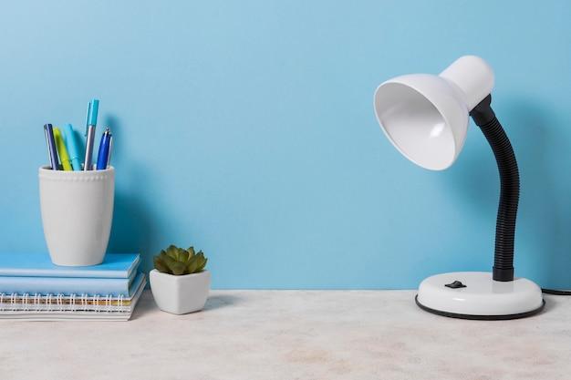 Arreglo de escritorio con lámpara y planta. Foto Premium