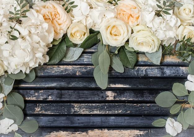 Arreglo floral de hermosas rosas blancas sobre fondo de madera, concepto de flores Foto gratis