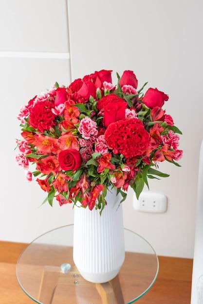 Arreglo floral de rosas rojas en una bonita sala de estar Foto Premium