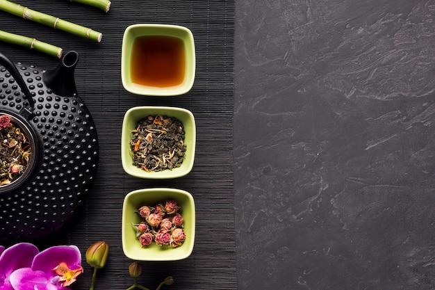 Arreglo de flores secas y hierbas de té en mantel negro sobre fondo Foto gratis