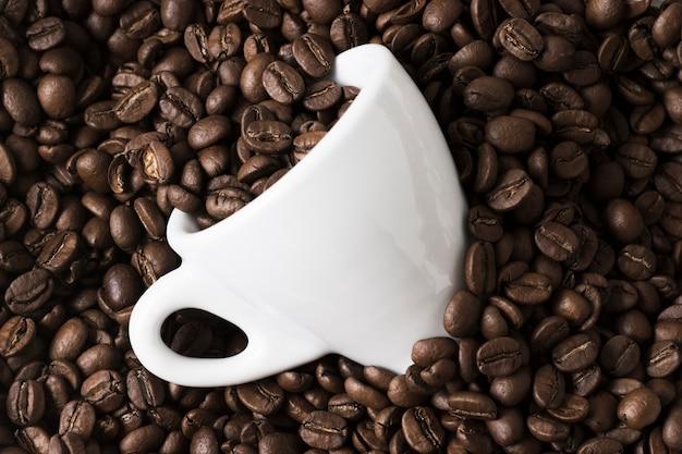 Arreglo de granos de café tostados y taza blanca Foto gratis