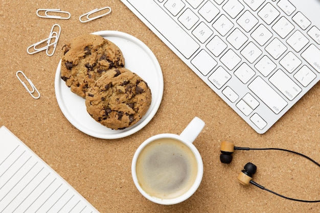 Arreglo de lugar de trabajo moderno con plato de galletas Foto gratis
