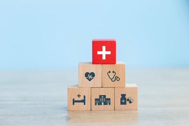 Arreglo de mano apilar bloque de madera con el icono de salud médica. Foto Premium