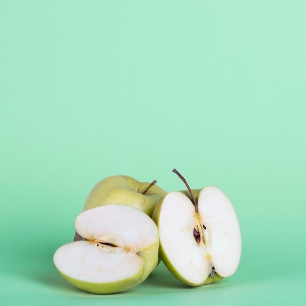 Arreglo con medias manzanas sobre fondo verde Foto gratis