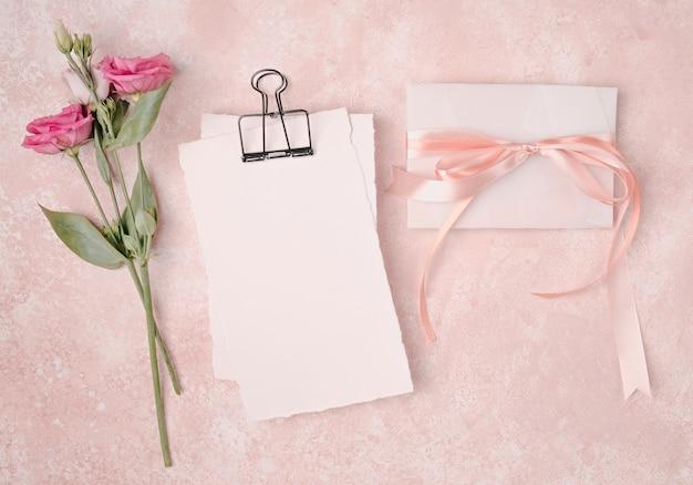 Arreglo plano de boda con invitación y flores. Foto gratis