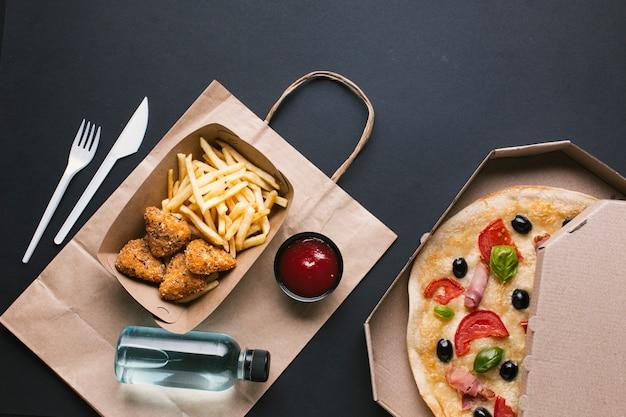 Arreglo plano con crujiente y pizza Foto gratis