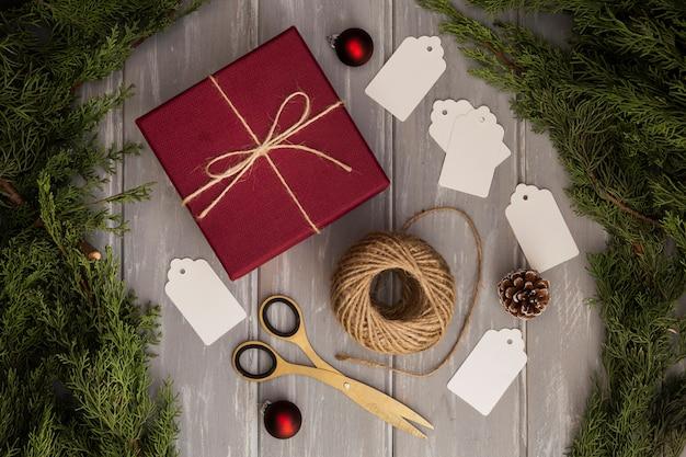 Arreglo plano con presente y árbol de navidad Foto gratis