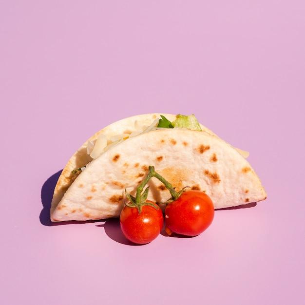 Arreglo con taco y tomates cherry sobre fondo morado Foto gratis