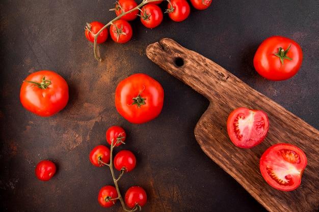 Arreglo de tomates sobre fondo oscuro Foto gratis