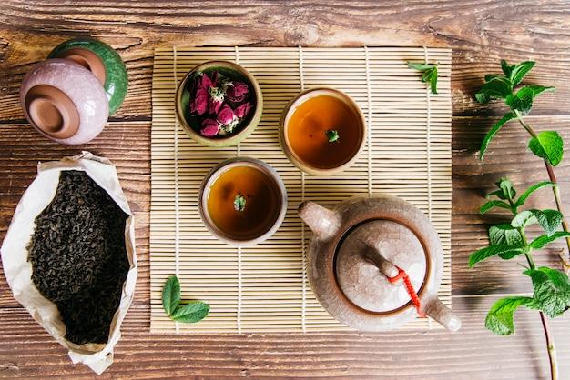 Arreglo tradicional de la ceremonia asiática del té con pétalos de rosa y ramita de menta en el escritorio de madera Foto gratis