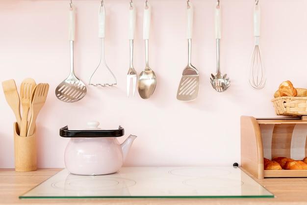 Arreglo con utensilios de cocina y tetera. Foto gratis
