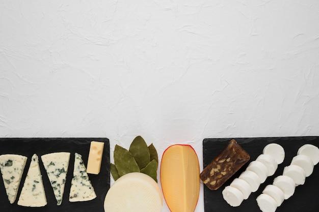 Arreglo de varios quesos en pizarra negra con hojas de laurel en la esquina de la superficie blanca Foto gratis