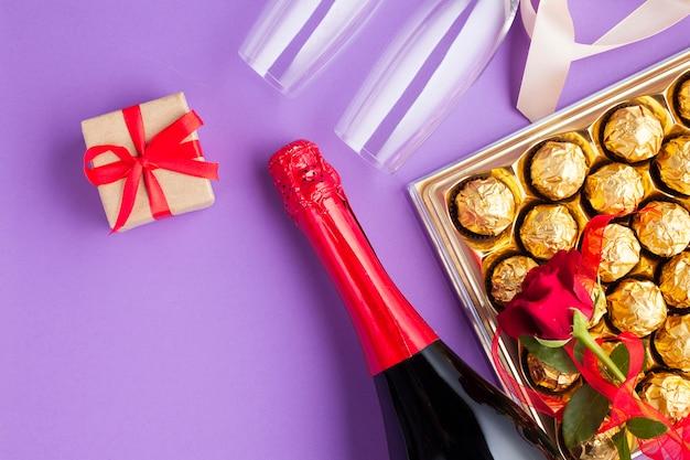 Arreglo vista superior con caja de chocolate y botella de vino. Foto gratis