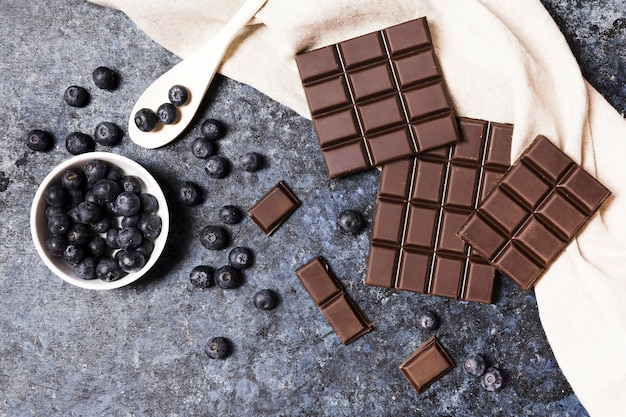 Arreglo vista superior con chocolate negro y arándanos. Foto gratis