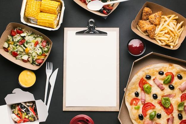 Arreglo de vista superior con comida y portapapeles Foto gratis