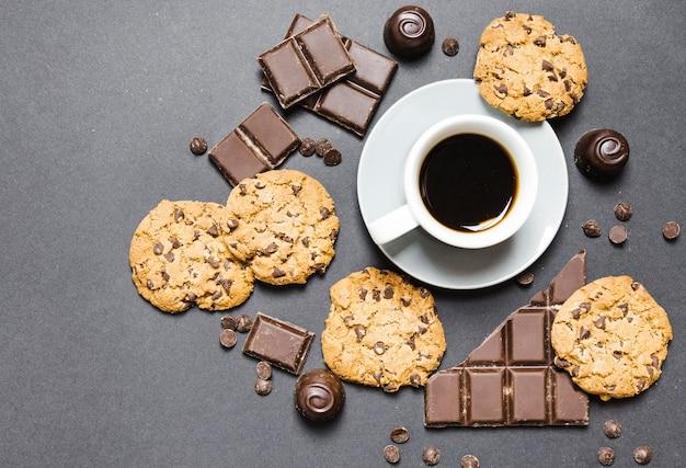 Arreglo vista superior con galletas, dulces de chocolate y café. Foto gratis