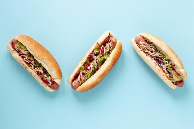 Arreglo de vista superior con hot dogs y fondo azul Foto Premium