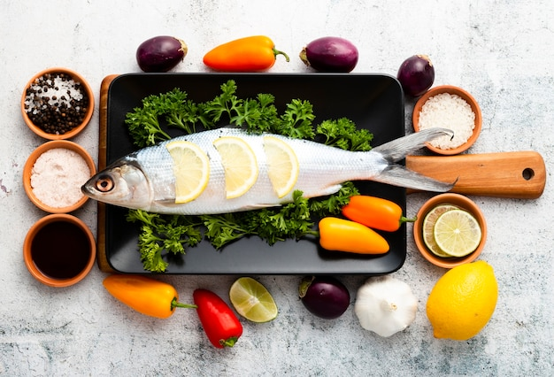 Arreglo de vista superior con pescado y verduras Foto gratis