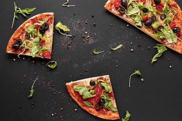 Arreglo de vista superior con rebanadas de pizza Foto gratis