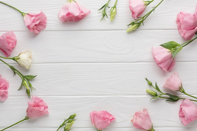 Arreglo de vista superior con rosas rosadas sobre fondo de madera Foto gratis