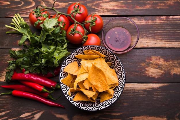 Desde arriba arreglo de nachos y verduras. Foto gratis