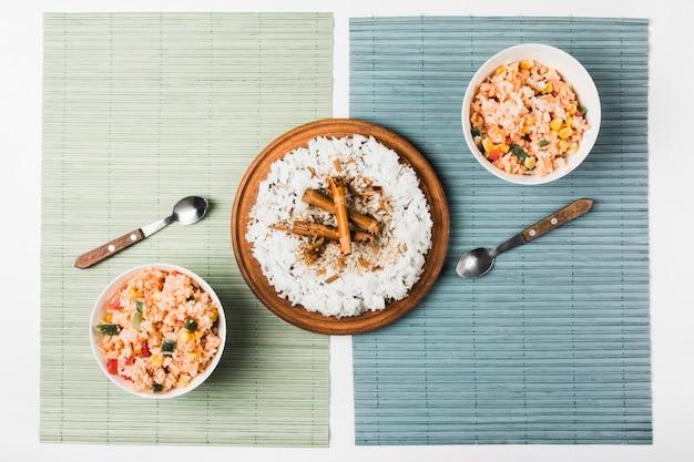 Arroz chino frito y al vapor con palitos de canela en mantel Foto gratis