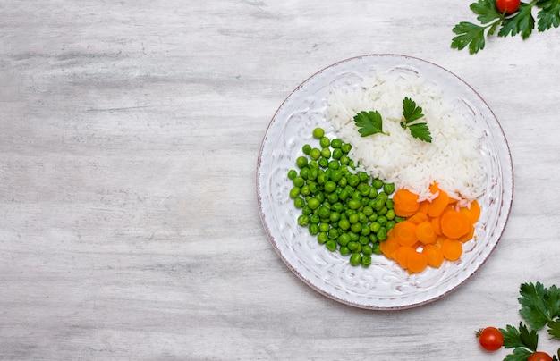 Arroz cocido con verduras y perejil en un plato en la mesa Foto gratis
