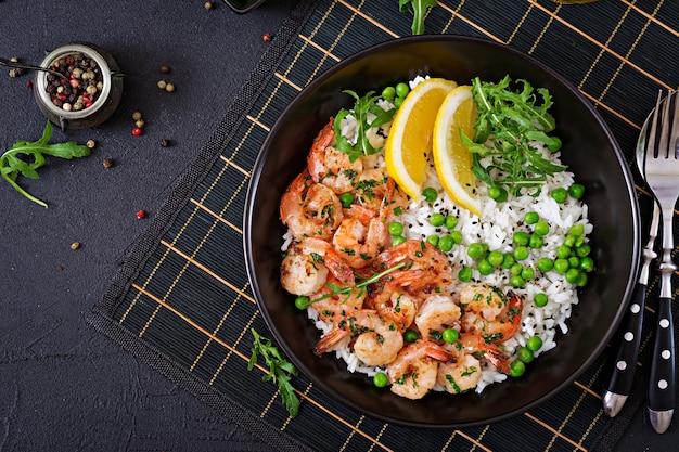 Arroz con guisantes verdes, camarones y rúcula en un recipiente negro. comida sana. cuenco de buda Foto Premium